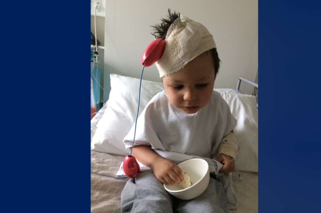 cem has bandages around his head and recovers from surgery in his hospital bed