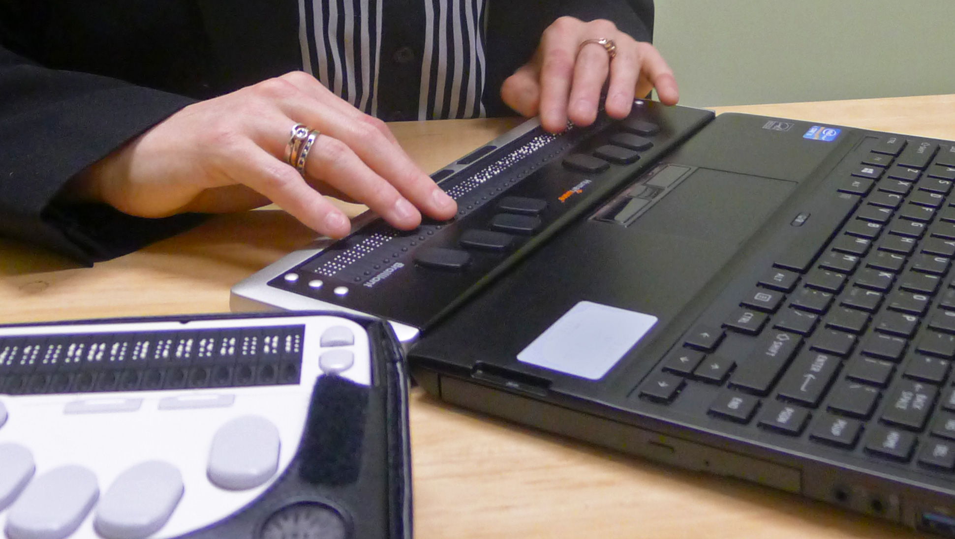 A person's hands reading a refreshable braille display, and a braille note taker device is also in scene.